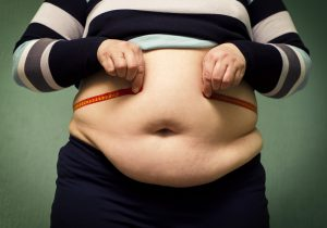 Obesity with person tying tape measure around waist