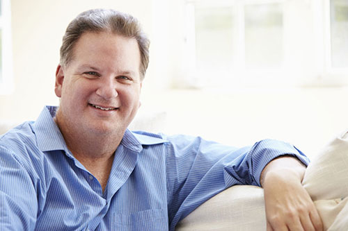man sitting on lounge, has had gastric sleeve surgery