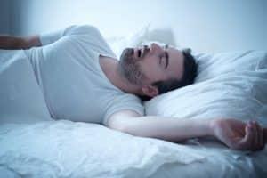 man sleeping snoring in bed