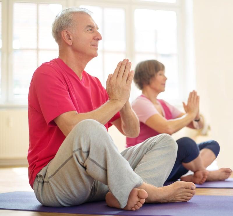 Senior couple exercising in yoga class